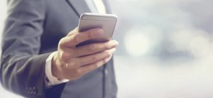 Man in a suit holding a smart phone