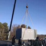 Technicians guiding HVAC unit on a crane