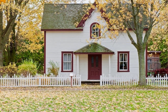 The outside view of a cozy-looking house surrounded by autumn leaves.