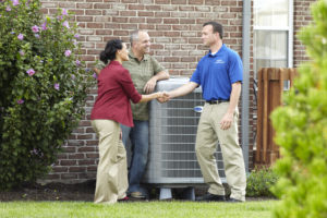 Technician shaking woman's hand with man by central AC unit