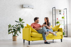 Man and woman seated on yellow couch with wall unit