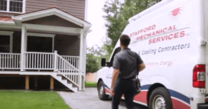A Stafford Mechanical Technician arrives at a residential job, and approaches the house from his van.